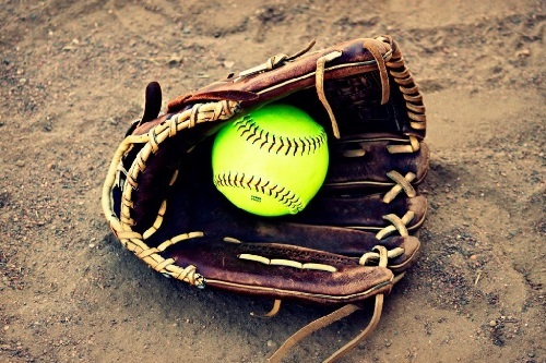 Softball Glove With Ball Displayed On Dirt